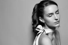 Schönes leichtes Mädchen mit silk Bogen auf der rechten Schulter Lizenzfreies Stockfoto