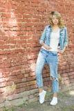 Schönes lustiges blondes Mädchen mit den großen Lippen mit reizend Lächeln-, Tragenjeans und einem weißen Hemd gehend in das Stad Stockfotografie