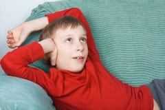 Schönes lustiges Kind, welches die helle rote Strickjacke stillsteht auf einem Sofaträumen trägt Stockfotografie