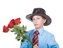 Schönes lustiges romantisches Jungentragen gekleidet einen Blumenstrauß des Lächelns der roten Rosen formal, halten Stockfotografie