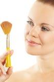 Schönes Mädchen über einen Pinsel für Kosmetik lizenzfreies stockfoto