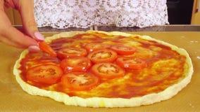 Schönes Mädchen übergibt die Platzierung von Tomatenscheiben auf selbst gemachten Pizza Margarita stock footage