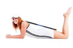 Schönes Mädchen auf dem Fußboden mit einem Tennis racke Stockfotografie
