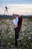 Schönes Mädchen auf dem Gänseblümchenblumenfeld Hände oben Späte Zeit stockbild