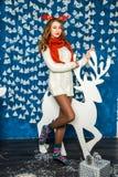 Schönes Mädchen auf dem Hintergrund der blauen Wand mit Girlanden und Stockfotos