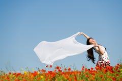 Schönes Mädchen auf dem Mohnblumegebiet stockfoto