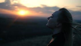 Schönes Mädchen auf dem Sonnenunterganghintergrund stock video footage