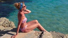 Schönes Mädchen auf dem Strand durch das Meer stock video footage