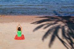 Schönes Mädchen auf dem Strand mit dem Farbton der Palme Stockfotos