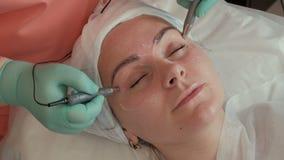 Schönes Mädchen auf dem Verfahren von Cosmetology im Schönheitssalon Die Hände der Kosmetikerführungselektroden microcurrent MA stock video footage