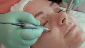 Schönes Mädchen auf dem Verfahren von Cosmetology im Schönheitssalon Die Hände eines Kosmetikers geben Elektroden um die Augen vo stock video