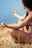 Schönes Mädchen auf der Seeküste in einer Yogahaltung Stockbilder