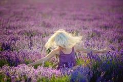 Schönes Mädchen auf einem Gebiet des Lavendels auf Sonnenuntergang lizenzfreie stockfotos