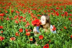 Schönes Mädchen auf einem Mohnblumegebiet Stockfotografie