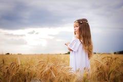 Schönes Mädchen auf einem Weizengebiet mit dem langen Haar und einem Kranz, der auf dem links schaut lizenzfreies stockbild