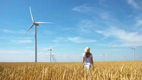Schönes Mädchen auf gelbem Feld des Weizens mit Windmühlen für Produktion des elektrischen Stroms stockbilder