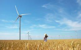 Schönes Mädchen auf gelbem Feld des Weizens mit Windmühlen für Produktion des elektrischen Stroms lizenzfreie stockbilder