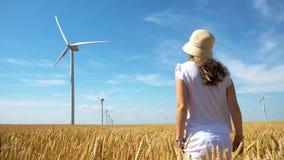 Schönes Mädchen auf gelbem Feld des Weizens mit Windmühlen für Produktion des elektrischen Stroms lizenzfreies stockfoto