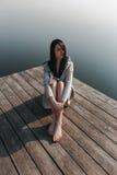 Schönes Mädchen auf hölzernem Pier nahe dem Wasser Stockbild