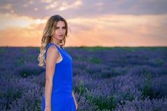 Schönes Mädchen auf Lavendel Gebiet bei Sonnenuntergang lizenzfreie stockbilder