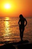 Schönes Mädchen auf Sonnenuntergang an der Küste Stockbild