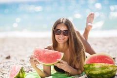 Schönes Mädchen auf Strand Wassermelone essend Stockbild