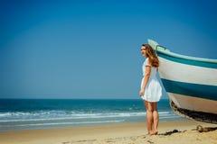 Schönes Mädchen auf tropischem Strand nahe dem Boot des Fischers mit Hintergrund von Ozean lizenzfreies stockfoto