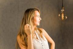 Schönes Mädchen betrachtet die Lampe lizenzfreie stockbilder