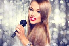 Schönes Mädchen, das über Feiertagshintergrund singt Stockfotos