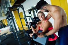 Schönes Mädchen, das Übungen mit persönlichem Trainer tut Lizenzfreies Stockfoto
