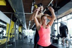 Schönes Mädchen, das Übungen mit persönlichem Trainer tut Stockbild