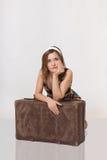 Schönes Mädchen, das auf altem Koffer sich lehnt lizenzfreie stockfotografie