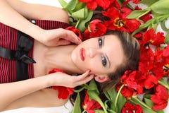 Schönes Mädchen, das auf Blumen liegt lizenzfreies stockbild