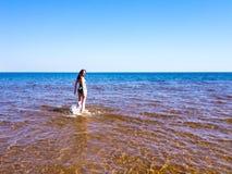 Schönes Mädchen, das auf das Wasser geht Lizenzfreie Stockfotos