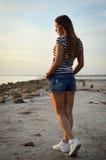 Schönes Mädchen, das auf dem Aufpassen des felsigen Strandes geht Stockfotografie