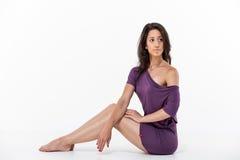 Schönes Mädchen, das auf dem Boden im lila Kleid sitzt Stockbild