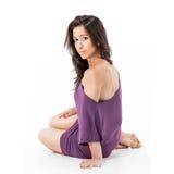 Schönes Mädchen, das auf dem Boden im lila Kleid sitzt Lizenzfreies Stockbild