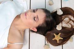 Schönes Mädchen, das auf dem Boden mit Muscheln in ihrem Haar liegt Porträt studio Stockfotos