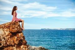 Schönes Mädchen, das auf dem clitt nahe Meer sitzt Lizenzfreie Stockfotografie
