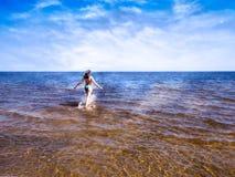 Schönes Mädchen, das auf dem Glänzen des transparenten Wassers von blauem Meer geht stockbild