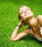 Schönes Mädchen, das auf dem Gras liegt lizenzfreies stockfoto