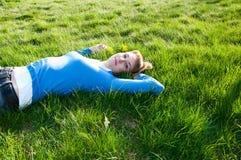 Schönes Mädchen, das auf dem Gras liegt Stockfotos