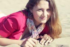 Schönes Mädchen, das auf dem Sand sitzt Lizenzfreie Stockfotos