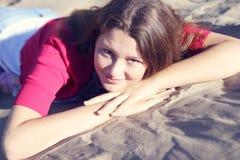 Schönes Mädchen, das auf dem Sand sitzt Stockbild