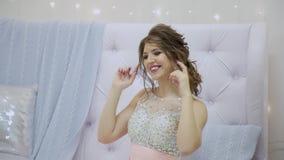 schönes Mädchen, das auf dem Sofa im Dekor des neuen Jahres sitzt stock footage