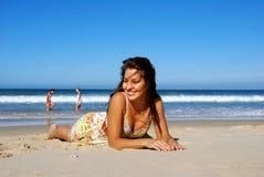 Schönes Mädchen, das auf dem Strand liegt Lizenzfreie Stockfotos