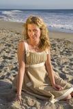 Schönes Mädchen, das auf dem Strand sitzt Stockfotografie