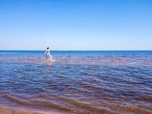 Schönes Mädchen, das auf dem Wasser läuft lizenzfreie stockfotografie