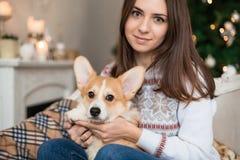 Schönes Mädchen, das auf der Couch mit einer Welpe Waliser-Corgi-Wolljacke auf dem Hintergrund von Weihnachten sitzt lizenzfreie stockfotos
