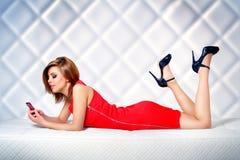 Schönes Mädchen, das auf der Couch mit Mobiltelefon liegt Lizenzfreie Stockbilder